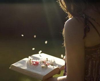 Девушка держит книгу с лепестками