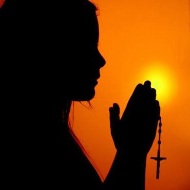Девушка с крестиком молится