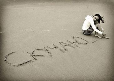 """Девушка сидит на песке с надписью """"скучаю"""""""