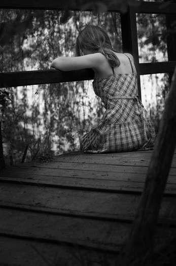 Грустная девушки сидит на мосту