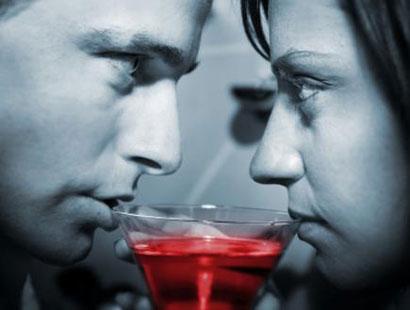 Мужчина и девушка пьют из одного бокала