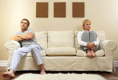 Мужчина и женщина сидят на разных углах дивана