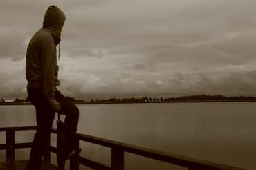 Парень смотрит в даль на берегу