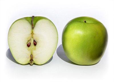 Зеленое яблоко и половинка яблока