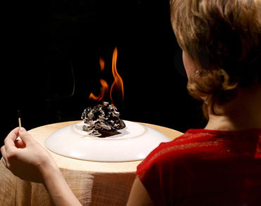 Женщина жгет бумагу на столе