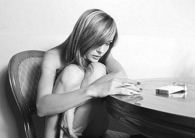 Девушка сидит за столом, подобрав ноги