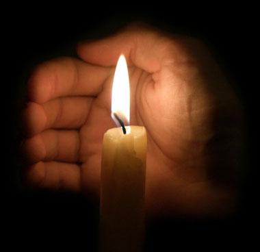 Огонь свечи прикрывает рука