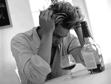 Парень сидит за столом с бутылкой и бокалом