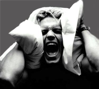 Парень закрыл уши подушками и кричит