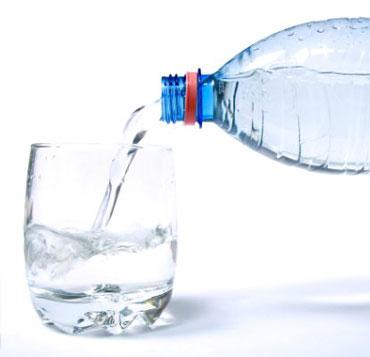 Вода льется из бутылки в стакан