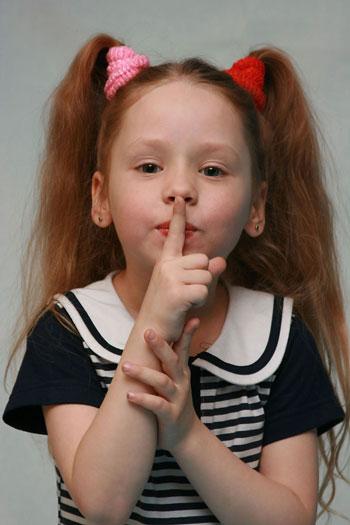 Девочка прижала палец к губам