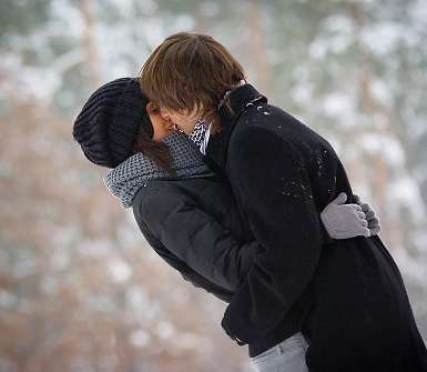 Парень целует девушку на улице зимой