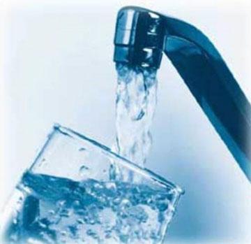 Вода из крана льется в стакан