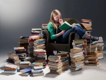 Девочка читает книгу, вокруг много книг