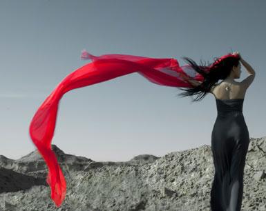 Девушка держит шарф, который развивается на ветру