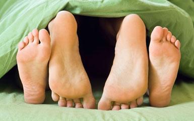 Пятки парня и девушки торчат из-под одеяла