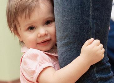 Ребенок держится за ногу матери