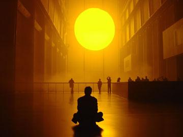 Человек в позе лотоса смотрит на большое солнце