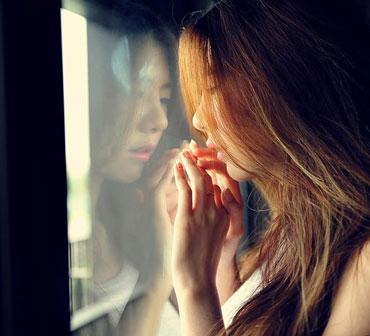 Девушка стоит у окна