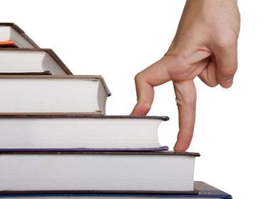 Пальцы руки поднимаются по лестнице из книг