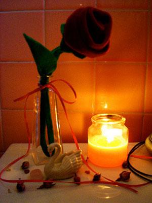 На столе роза, свеча, фигурка лебедя