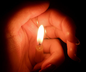 Церковная свеча прикрыта женской рукой