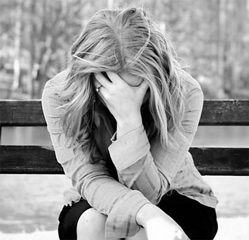 Девушка плачет на скамейке