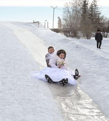 Молодожены катятся со снежной горки