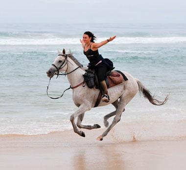 Женщина верхом на лошади едет вдоль моря