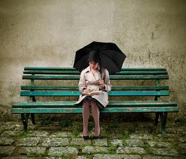 Девушка с зонтом сидит на скамейке