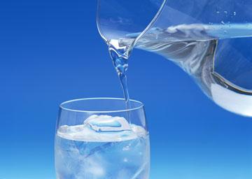 Вода льется из кувшина в стакан