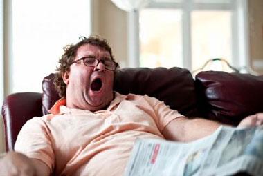 Толстый мужчина зевает
