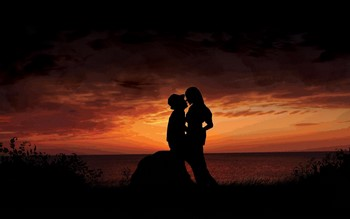 Парень и девушка обнимаются на закате