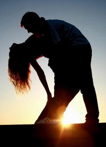 Парень обнимает девушку на закате