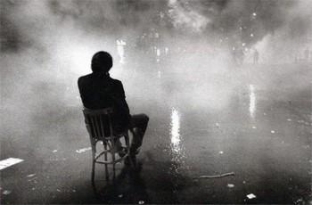 Парень сидит один на стуле на улице