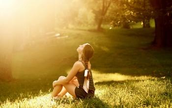 Девушка сидит в лесу на полянке