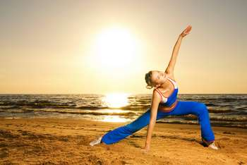 Девушка занимается гимнастикой на пляже