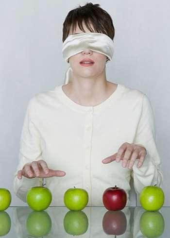 Девушка сидит с закрытыми глазами перед яблоками