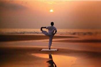 Мужчина делает гимнатиску на закате на пляже