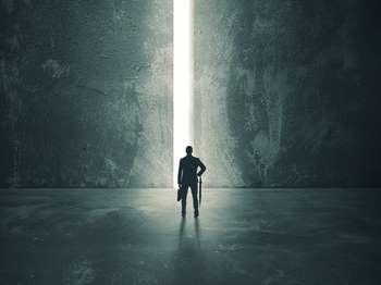 Мужчина стоит перед столбом света