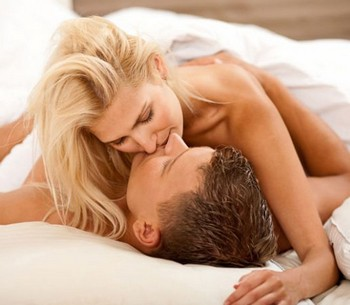 Девушка целует парня в постели