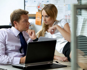 Девушка сидит на рабочем столе у мужчины