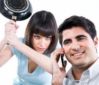 Девушка со сковородкой в руках за спиной у мужчины