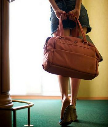 Девушка уходит с сумкой в руках