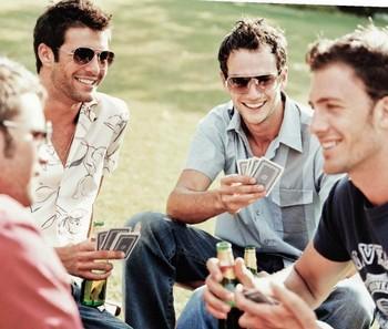 Друзья пьют пиво и играют в карты