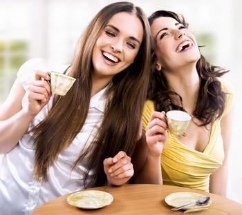 Две подруги пьют кофе и смеются