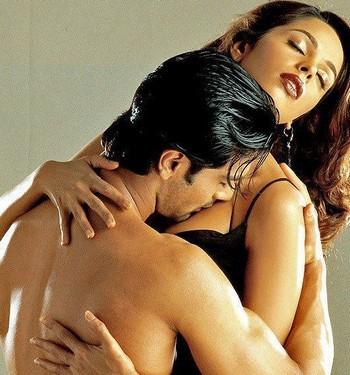 Мужчина целует женщине грудь