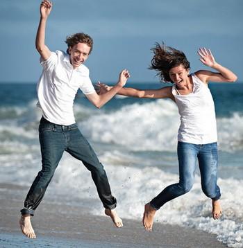 Мужчина и женщина прыгают на пляже