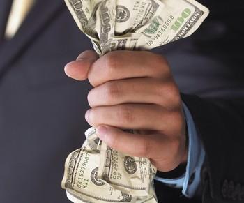 Мужчина мнет в руках деньги