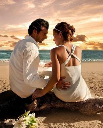 Мужчина с женщиной сидят на пляже на закате